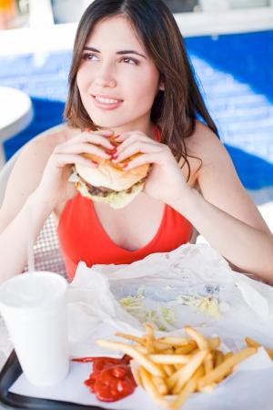 restuarant: Beautiful happy young latin girl eating hamburger at fast food restuarant Stock Photo