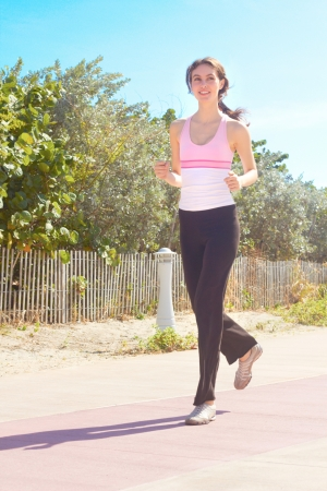 Full length of a active sporty female jogging. Vertical Shot. photo