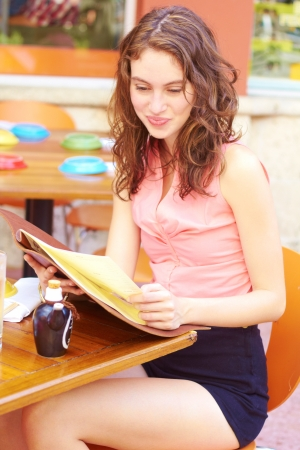 table skirt: Attractive young woman reading menu at restaurant table. Vertical Shot.