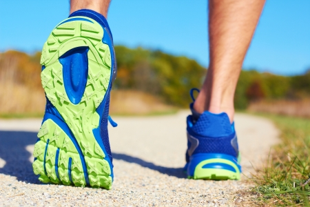 training shoes: Close up of man walking on nature trail near forest preserve. Color image, copy space, male walking outside on a beautiful day in nature.Horizontal