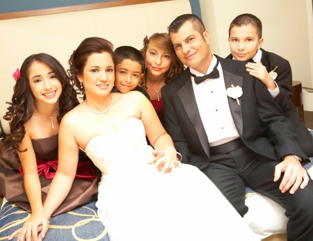Portrait of newly wedded couple with bridesmaids and groomsmen sitting on bed. Horizontal shot. photo