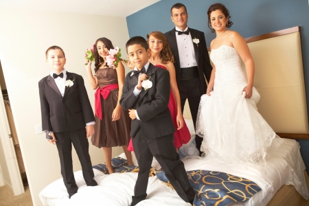 Portrait of newly wedded couple with bridesmaids and groomsmen standing on bed. Horizontal shot. photo