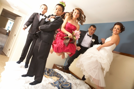 Full length portrait of newly wedded couple with bridesmaids and groomsmen jumping on bed. Horizontal shot. photo