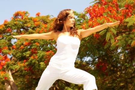 off shoulder: Young female in an off shoulder outfit doing stretching exercise on a sunny day with trees in background. Horizontal shot.