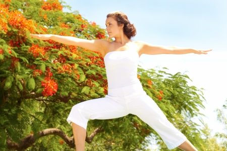 off the shoulder: Young female in an off shoulder outfit stretching arms on a sunny day with trees in background. Horizontal shot. Stock Photo