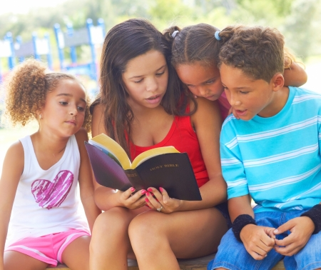 bible: Teenage girl reads to her three siblings from the Holy Bible on park bench. Horizontal shot.