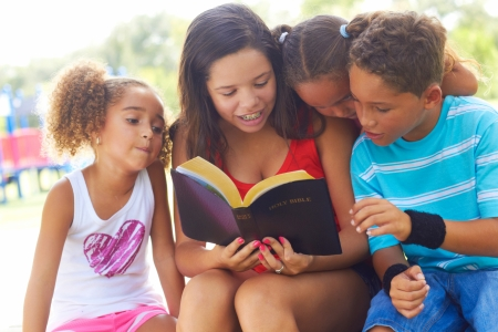holy bible: Teenage girl reads to her three siblings from the Holy Bible on park bench. Horizontal shot.