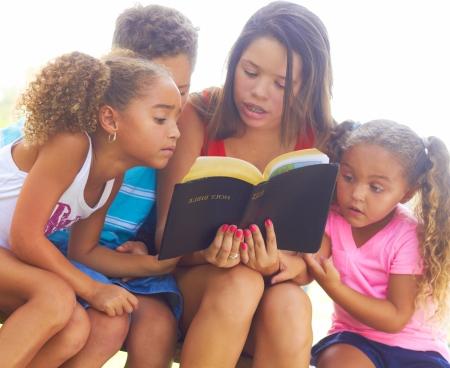 leyendo la biblia: Adolescente lee a sus tres hermanos de la Santa Biblia en banco de parque. Tiro horizontal. Foto de archivo