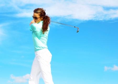 Pretty female golfer taking a golf swing in the rough. photo