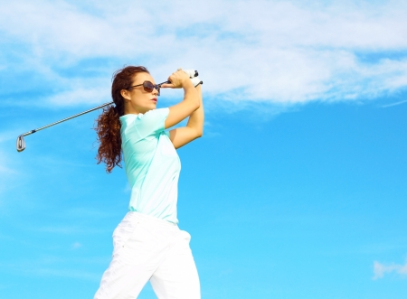 Pretty female golfer taking a golf swing in the rough. photo
