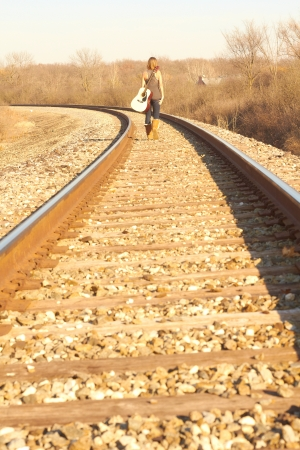 girl playing guitar: Young Lady Walking On Railroad Tracks With Guitar. Stock Photo
