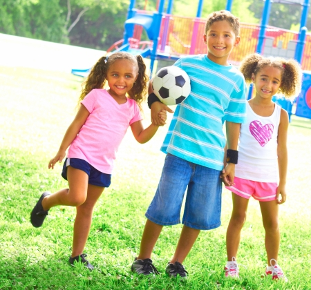 Full length portrait of happy little children with soccer ball at park. Horizontal shot. photo