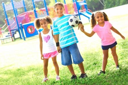 famille africaine: Portrait en pied d'heureux petits enfants avec un ballon de soccer au parc. Prise de vue horizontale.