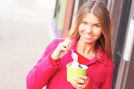 Pretty happy young pretty female eating frozen yogurt.  photo