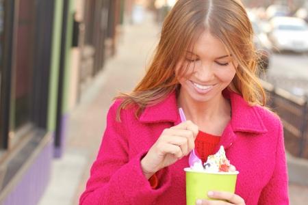 comida congelada: Bastante feliz joven muy femenina comer yogur congelado. Tiro horizontal.