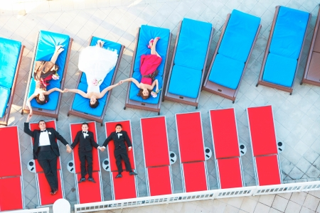 High angle view of newly wedded couple with bridesmaids and groomsmen lying on lounge chairs. horizontal shot. photo