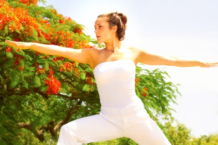 off the shoulder: Young fitness woman in an off shoulder casual wear stretching arms with trees in background. Horizontal shot. Stock Photo