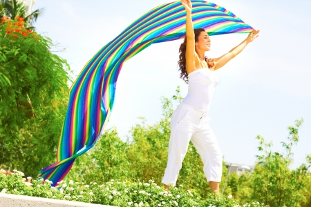 off the shoulder: Young woman in casual wear holding out a colorful striped cloth while standing in a park. Horizontal shot.