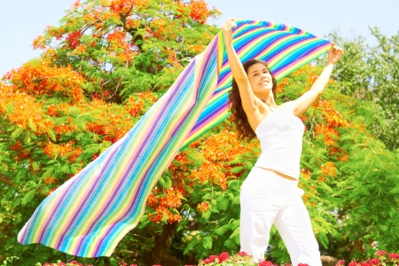 trees photography: Pretty young woman in casual wear holding a colorful striped cloth with trees in background. Horizontal shot.