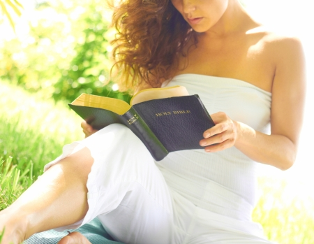 off the shoulder: Cropped image of female in casual wear holding a holy bible. Horizontal shot. Stock Photo