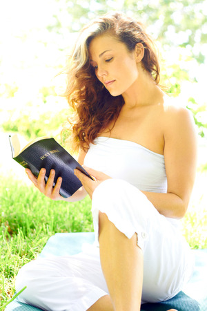 off shoulder: Beautiful young woman in casual wear reading bible while sitting in park. Vertical shot.