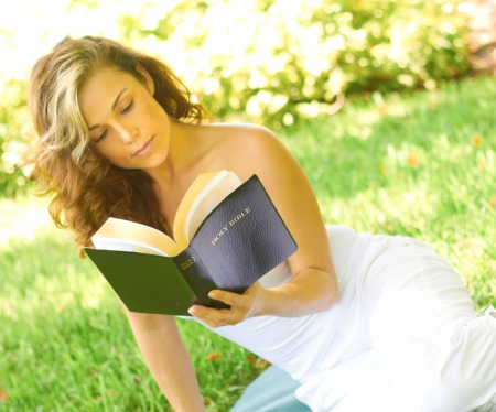 off the shoulder: Attractive young woman reading bible while sitting in park. Horizontal shot. Stock Photo