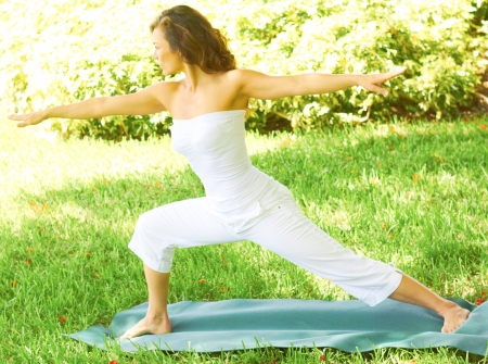 off the shoulder: Full length of young fitness female stretching arms while standing on exercise mat in park. Horizontal shot.