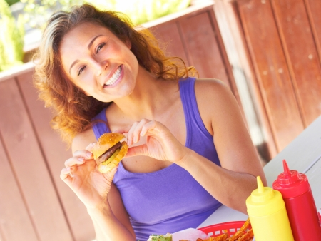 Portrait of beautiful young woman smiling while having a mini hamburger. Horizontal shot. photo