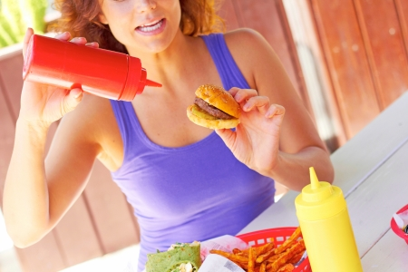 Midsection of young woman having mini burger with tomato ketchup. Horizontal shot. photo