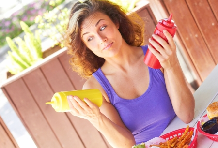 Young woman with raised eyebrows looking at mustard while holding tomato ketchup bottle. Horizontal shot. photo