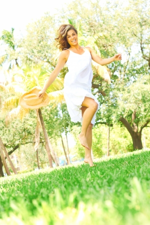 jovial: Full length portrait of a jovial young woman dancing in park. Vertical shot.