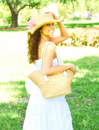 sunhat: Portrait of happy young woman wearing sunhat looks over shoulder while carrying a handbag. Vertical shot.