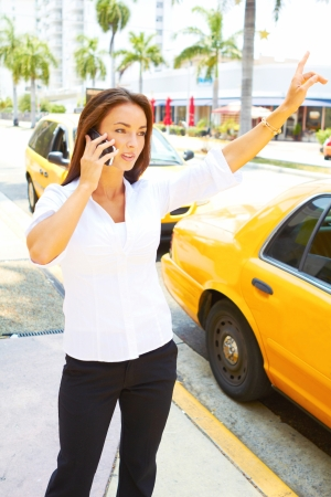 yellow taxi: beautiful young business female talking on cell phone in front of yellow taxi. Stock Photo