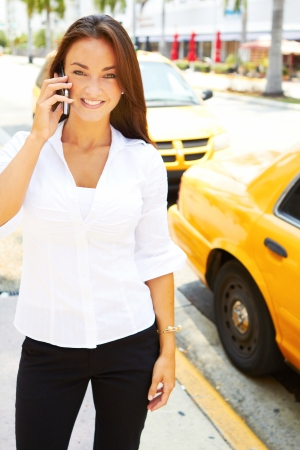 beautiful young business female talking on cell phone in front of yellow taxi. photo