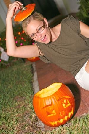 public celebratory event: Portrait of playful young woman sitting besides an anthropomorphic Halloween pumpkin lantern. Vertical shot. Stock Photo