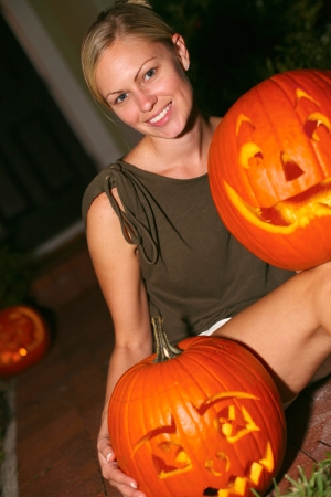 Portrait of beautiful young woman with anthropomorphic Halloween jack-o-lantern. Vertical shot. photo
