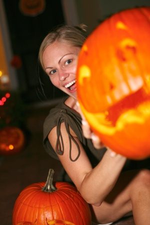 anthropomorphic: Portrait of a cheerful young woman holding an anthropomorphic Halloween pumpkin lantern. Vertical shot.