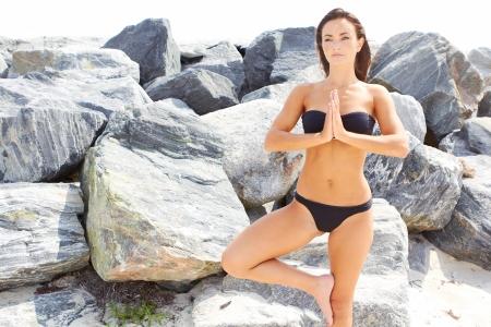 buena postura: hermosa chica en buena forma f�sica que hace yoga por las piedras