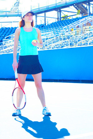 Full length of young female sportswoman holding tennis racquet and ball while standing in court. Vertical shot. photo