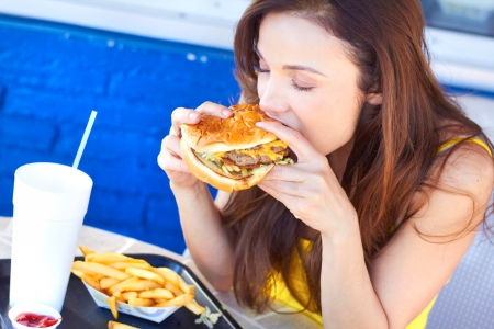 unhealthy living: Beautiful young lady eating a tasty burger at an outdoor cafe. Horizontal Shot.