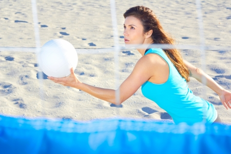 Young woman playing volleyball on beach. Horizontal Shot.  photo