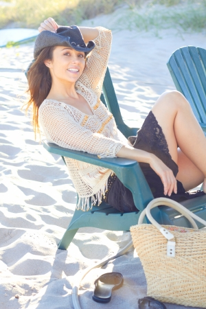 Portrait of pretty young woman in a cowboy hat relaxing on beach. Vertical Shot. photo