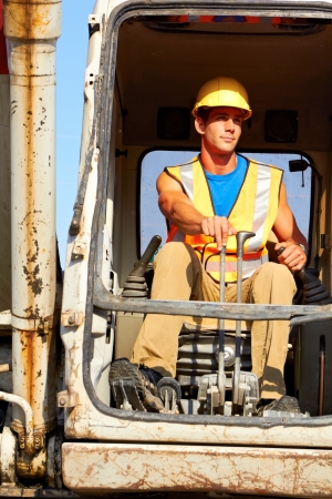 Portrait of young construction worker driving forklift, front view photo