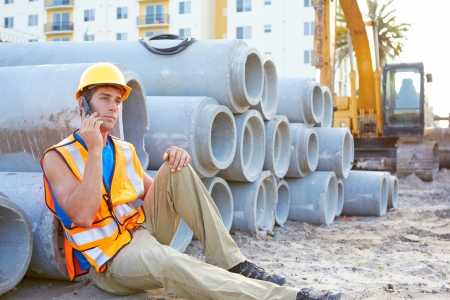 construction machinery: Young construction worker on cell phone at construction site