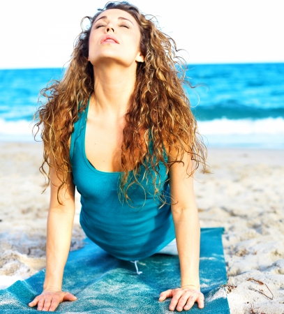 beautiful girl doing yoga on the sand at the beach photo