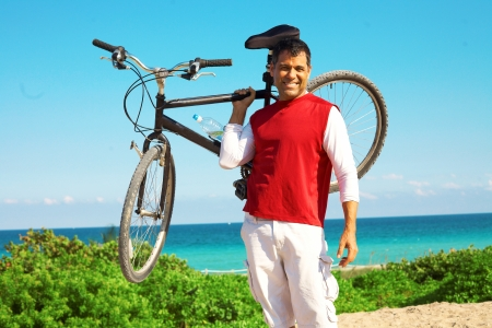 Full length of mid adult hispanic man in casual wear lifting a mountain bike holding up photo