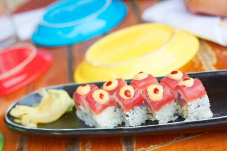 plating: Sushi roll with tuna, avocado, spicy mayo, ginger, wasabi surrounded by colorful plating.