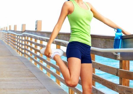 relaxation exercise: Healthy young woman stretching her leg during exercise on boardwalk. Horizontal shot.