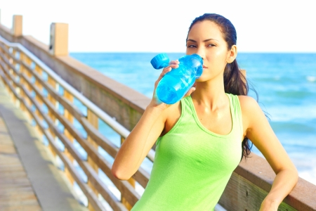body concern: Healthy young woman drinking from waterbottle on boardwalk. Horizontal shot. Stock Photo