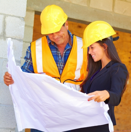 Happy Architect and foreman reviewing blueprint together at construction site.  photo